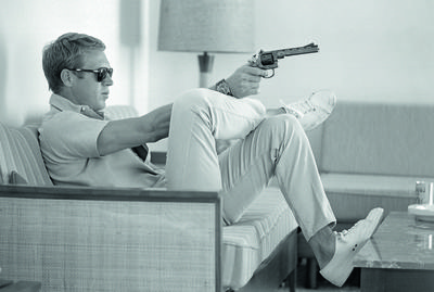 7. Steve McQueen aims a pistol in his living room